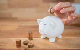 Close-up of hand inserting coin in piggy bank